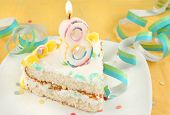 picture of birthday-cake  - slice of eight birthday cake with lit candle confetti and ribbon  - JPG