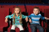 Little boy and girl attentively watching a movie