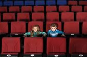 Little boy and girl watching a movie in empty cinema hall