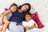 stock photo of pajamas  - Mother And Children Relaxing In Bed Wearing Pajamas - JPG