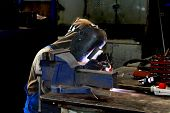 Welder Working In Production Workshop On A Workbench