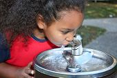 foto of drinking water  - Adorable five year old African American Girl drinking from water fountain - JPG
