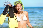 snorkeling fun on beach - woman showing fins, snorkel and mask while doing watersport on summer holidays travel vacation on Maui, Hawaii, USA. Beautiful young mixed race Asian Caucasian bikini model.