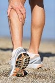 Muscle injury - Man running clutching his calf muscle after spraining it while out jogging on the be