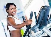 Happy woman exercising at the gym on an x-trainer