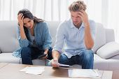 stock photo of receipt  - Desperate couple doing their accounts in the living room - JPG