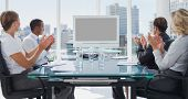 stock photo of applause  - Business people applauding during a video conference in the boardroom - JPG