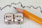 Dices Cubes With The Words Sell Buy, Pencil And Financial Chart. Selective Focus.