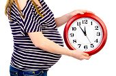 stock photo of expecting baby  - pregnant woman with clock isolated on a white background - JPG