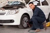 stock photo of auto garage  - Handsome young man using an air gun to change a tire at an auto shop - JPG