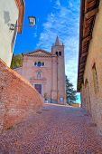 Vertical image of  red brick church and narrow cobblestone street in at medieval part of the town in