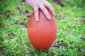 Hand on rugby ball on green grass background