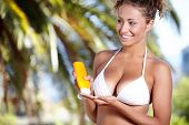 beautiful young woman in bikini smear protective cream on the skin on the beach under the palm