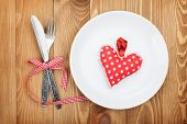 Valentine's Day toy heart over plate with silverware. On wooden table background