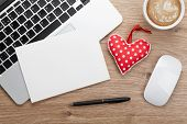 Valentine's day blank greeting card and toy heart over office workplace