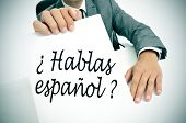 a man wearing a suit holding a signboard with the sentence hablas espanol? do you speak spanish? written in spanish on it