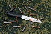 Military Sheathless Knife And Cartridges On Camouflage Backround
