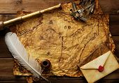 Sextant, spyglass and envelope on vintage map over wooden background