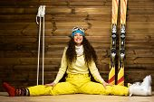 stock photo of ski boots  - Happy woman with skis and ski boots sitting on a floor near wooden wall - JPG