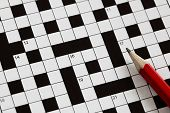 stock photo of riddles  - Solving a crossword puzzle with red pencil - JPG