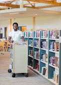 Portrait of young male librarian with trolley of books in bookstore