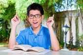 Young Chinese Asian student is successful at home with difficult homework assignment for school next