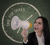 stock photo of indian money  - Businesswoman announcing time for taxes using megaphone - JPG