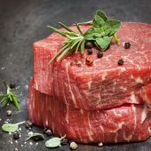Raw beef fillet steaks with herbs and spices.