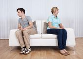 stock photo of opposites  - Brother and sister have had an argument and are sitting at opposite ends of a sofa - JPG