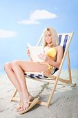 Beautiful Young Woman In Bikini Reading A Book