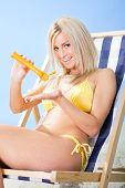 Beautiful Young Woman In Bikini Applying Suncream