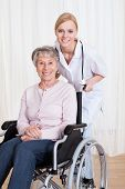 stock photo of handicapped  - Caring Doctor Helping Handicapped Senior Patient Indoors - JPG