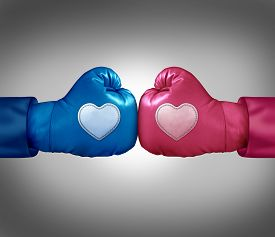stock photo of love hurts  - Fighting for love and relationship argument concept as blue and pink boxing gloves with heart shaped patches face off in a passionate couple dispute resulting in stress and possible separation or divorce - JPG
