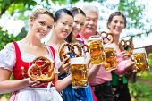 In Beer garden - friends, man and women in Tracht, Dirndl and Lederhosen drinking a fresh beer in Ba