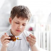 picture of cough syrup  - boy drinking cough syrup - JPG