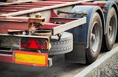 stock photo of big-rig  - Back part with taillight of empty truck cargo trailer on asphalt road - JPG