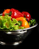 Freshly washed fresh vegetables in a metal colander isolated over black background.