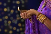Diwali or festive of lights. Traditional Indian festival, woman in sari hands holding oil lamp, with defocus light background.