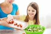 family, child, cooking and home concept - smiling little girl with mother adding tomatoes to salad in the kitchen