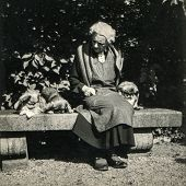 GERMANY, CIRCA 1930:  Vintage photo of elderly woman in apron sitting on bench with Pekingese dogs