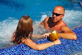 image of hot-tub  - Romantic couple with coconut drink relaxing in hot tub - JPG