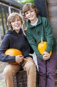 Two young happy smiling boys brothers outside with pumpkins