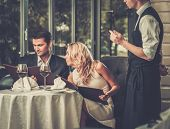 Cheerful couple with menu in a restaurant making order