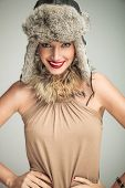 happy smiling beauty woman wearing fur hat and collar standing with hands on hips and looks to the camera