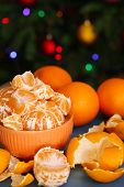 Sweet tangerines and oranges on table on Christmas tree background