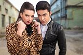 Young fashion couple posing near old factories, the woman is pulling her collar.