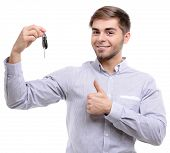 Businessman holding car key isolated on white