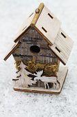 Miniature bird feeder on snowy surface