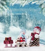 Winter holiday happy snow men with blur landscape on background. Concept of love and togetherness
