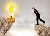 Businessman standing on the edge of mountain with an idea bulb on the other side